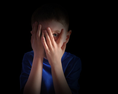 A child is hiding his eyes in the dark and looks scared or upset.