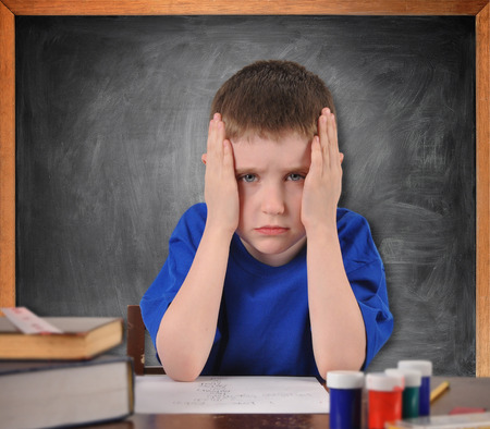 A young boy is sitting at a school desk looking tired and stressed from the lesson. photo
