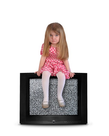 An upset young child is sitting on top of a television with snow on the screen for an entertainment or parenting concept. photo