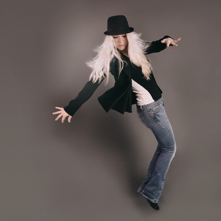 dancing club: A blond woman is standing in a dancing pose with a black hat and gray background for a club or entertainment concept  Stock Photo