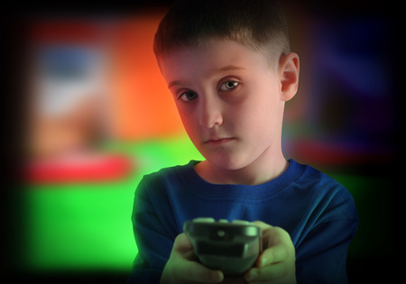 A young boy is watching a television screen turning the channel with a remote control for a tv effect on children or a communication concept   Stock Photo