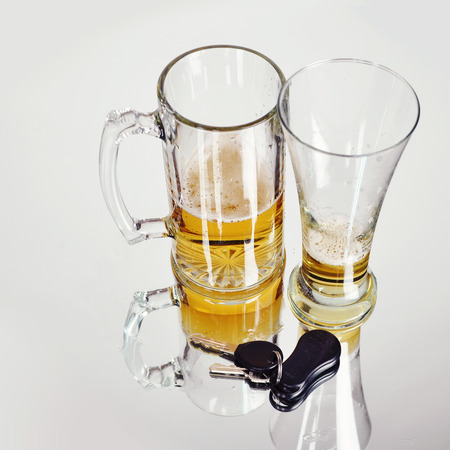 dwi: Two empty glass beer glasses with car keys on a white background for a dwi or drunk driving concept