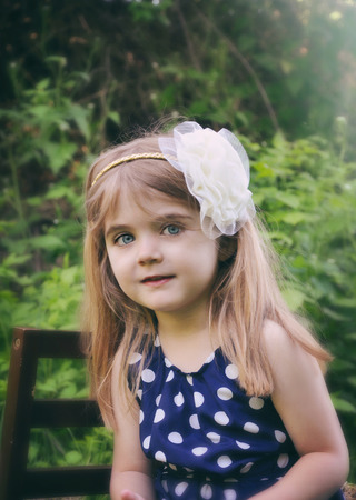 angelical: A pretty little girl is in the woods with green trees in the background  She is wearing a white headband and blue dress for a nature or season concept