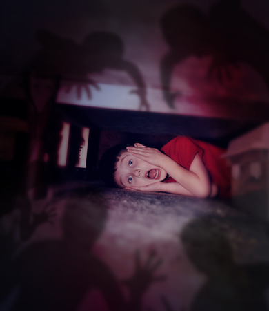 A young scared boy is hiding under a bed looking at black scary monster ghosts in fear for a bedtime or evil concept