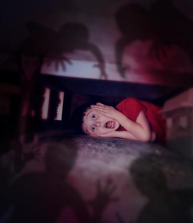 Un niño asustado joven se esconde debajo de la cama mirando negros fantasmas monstruo de miedo ante el temor por una hora de acostarse o el mal concepto Foto de archivo - 30140901