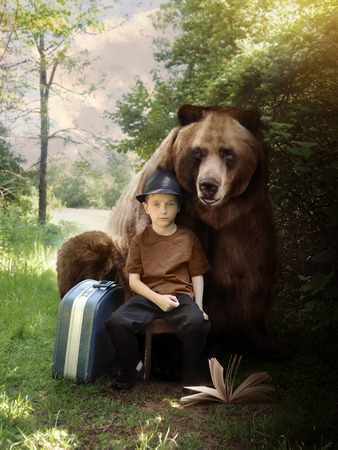 A young boy is sitting on a nature trail in the woods with a suitcase and book with a bear animal behind him for an imagination or travel concept