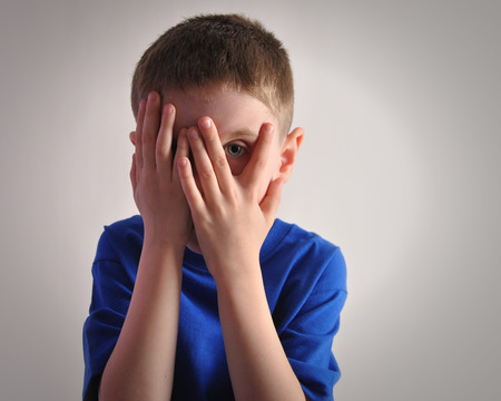 A child is hiding his eyes with his hands and looks scared or upset  The boy is isolated on a white background for a fear or sadness concept  Archivio Fotografico