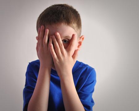 Un bambino si nasconde gli occhi con le mani e guarda spaventato o turbato Il ragazzo è isolato su uno sfondo bianco per un concetto di paura o tristezza Archivio Fotografico - 30140905