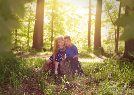 Two young children are sitting on a tree stump in the sunshine with green leaves in the woods for a relaxation or nature concept photo