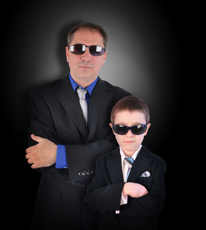 A father and son are wearing business suits with sunglasses pretending to be secret agents or bodyguards on a black background