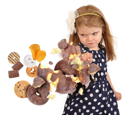 A little child is punching a chocolate donut as cookies and junk food are coming to her for a health or hunger concept on a white background