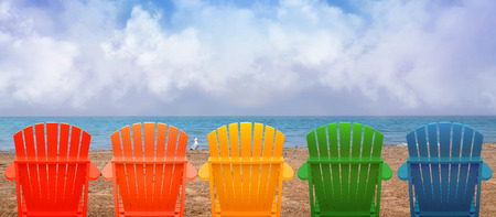 A rainbow of colors of wooden beach chairs are lined up along the water shore.