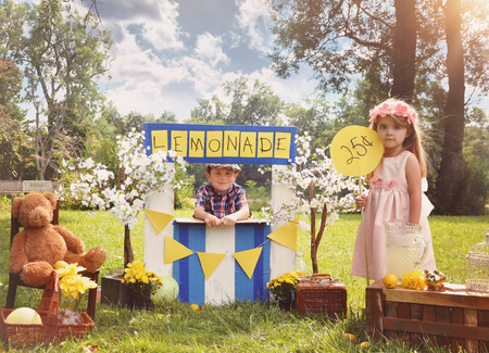 yard work: Two little kids are selling lemonade at a homemade lemonade stand on a sunny day with a price sign for an entrepreneur concept