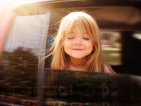 car on the road: A little girl is sticking her head out the car window and looking down for a road trip or travel concept