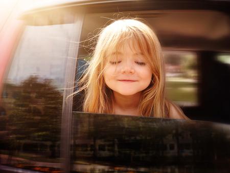 Een meisje steekt haar hoofd uit het autoraam en neer op zoek naar een road trip of reis-concept