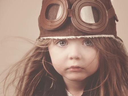 小さな女の子はキャリアまたは想像メッセージ アンティークな概念とゴーグルとパイロットの帽子を身に着けてください。