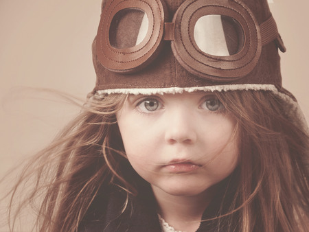A little girl is wearing a pilot hat with goggles with an antique concept for carrer or imagination message  Stock Photo