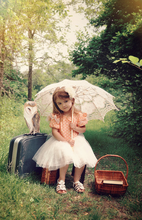 Beautiful portrait of a little girl with an umbrella and pet barn owl in the forest with a vintage look for a imagination or freedom concept  Stock Photo