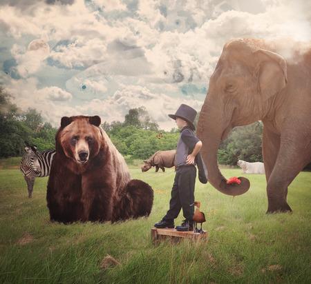 勇敢な子供は彼の周りクマ、象、シマウマ、想像力や創造的なコンセプトのクマなどの野生動物と自然のフィールドに立っています。