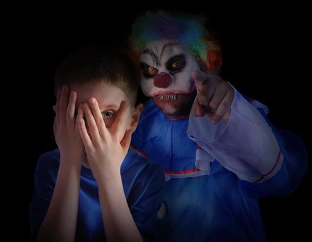 Een kind is het verbergen van zijn ogen in de donkere nacht en kijkt bang en boos op griezelige clown De jongen is geïsoleerd op een zwarte achtergrond voor een angst-concept Stockfoto