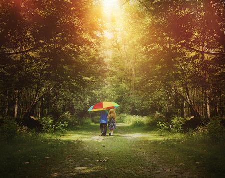 mujer alegre: Dos ni�os est�n caminando por un sendero de sol en el bosque que sostiene un paraguas del arco iris para una amistad, esperanza o concepto de la felicidad Foto de archivo