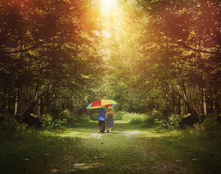 Two children are walking down a sunshine trail in the woods holding a rainbow umbrella for a friendship, hope or happiness concept