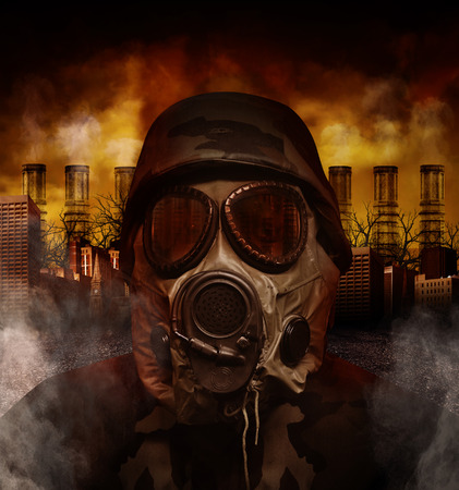 A soldier is wearing a gas mask in a polluted, scary city with smokestacks in the background for a war or hazard concept  Foto de archivo