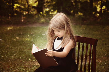 joy of reading: A smart little girl is reading an old book in nature with trees in the background for an education or knowledge concept  Stock Photo
