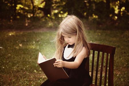 Een slim meisje is het lezen van een oud boek in de natuur met bomen op de achtergrond voor een opleiding of kennis concept Stockfoto