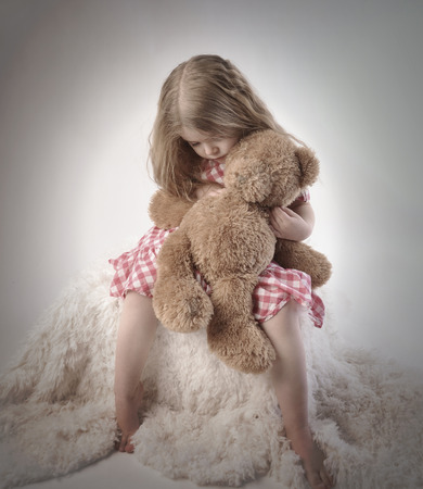 A sad little girl is holding a stuffed teddy bear on an isolated background for a timeout or emotion concept   Stockfoto