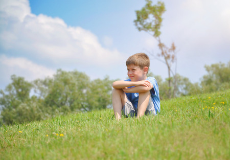 A young boy is sitting on a green grass hill and thinking on a hot summer day for a childhood or relaxation concept.