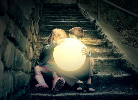 子供たちは、環境についての天候や季節の概念のためのウェット暗い階段の上、明るい黄色の輝く太陽を保持しています。 写真素材