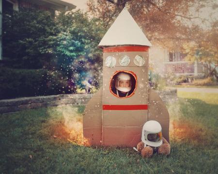 Een jonge jongen zit in een kartonnen ruimteraket schip met een astronaut helm op. Hij is in de voortuin verbeelding is hij in de ruimte met sterren.