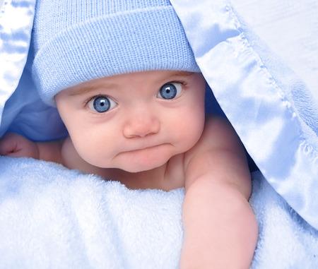 어린 소년 아기에 모자와 파란색 담요 아래에 숨어있다. 그는 카메라를 응시하고 자신의 배에 포즈입니다.