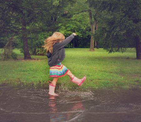 작은 아이는 외부의 장난이나 행복 개념에 대한 분홍색 고무 부츠와 함께 비 웅덩이에 튀는입니다.