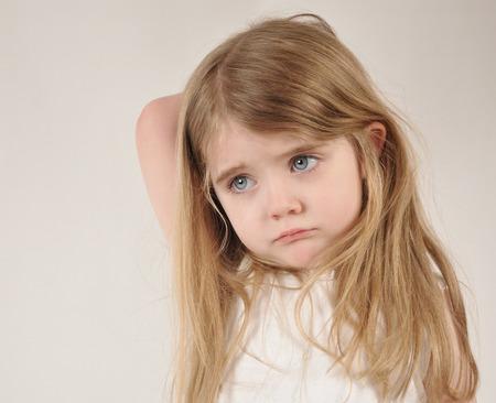 asustado: Un ni�o peque�o se ve triste y frustrado. La ni�a tiene su mano sobre su cabeza por un concepto de crianza o cansado.