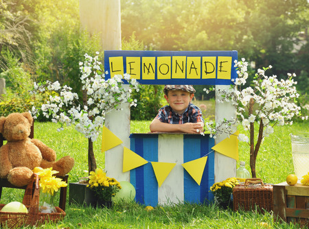 A little boy has an outdoor  homemade lemonade stand with a sign and he looks happy for a small business or money concept.