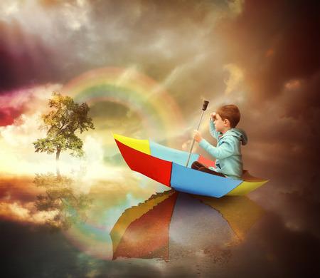 Ein kleines Kind sitzt in einem Regenschirm Boot schaut auf einen entfernten Baum des Lichtes mit einem Regenbogen für eine Phantasie oder Freiheit Konzept. Standard-Bild