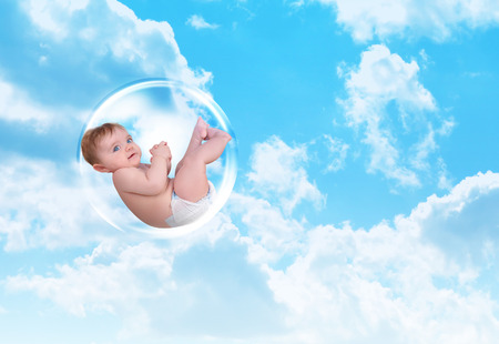 A young white baby is floating in a bubble in the sky with clouds. Symbolizes protection and security. photo