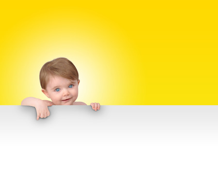 advertise: A young baby is holding a white isolated sign. Add your message in the blank copyspace.