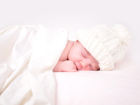 A young baby is sleeping on a white bed with a blanket. photo