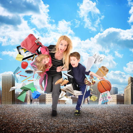 escuelas: Una madre llega tarde a la escuela y el trabajo, mientras que corriendo con sus hijos para un concepto de estr�s divertida con una ciudad en el fondo. Hay objetos que vuelan lejos de ellos. Foto de archivo