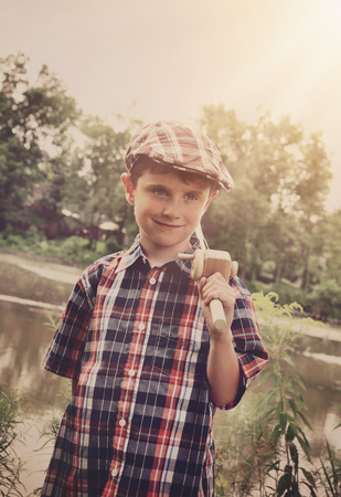 5 6 years: A young boy is wearing a cap hat and holding a wooden fishing pole by a pond of water for an activity or memory concept. Stock Photo