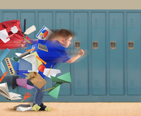 A school boy is running late with school supplies falling out of his book bag in a hallway with lockers in the background for an education or academic concept. Stock Photo