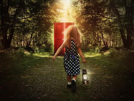imaginacion: Un ni�o est� caminando en el bosque sosteniendo una luz y mirando a una puerta roja que brilla intensamente en el camino para un concepto de misterio o de la imaginaci�n.
