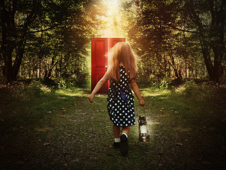 A little child is walking in the woods holding a light and looking at a glowing red door on the path for a mystery or imagination concept.