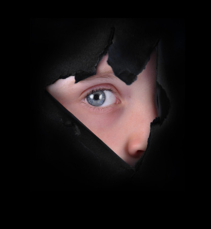 A child is peeking through a ripped paper hole on a black background for a secret or mystery concept
