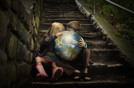 discover: Children are holding the planet earth on wet dark stairs for a weather or season concept about the enviornment. Stock Photo