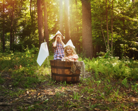 people and nature: A little boy and girl are pretending to fish in a wooden barrel boat in the nature woods with a real fish being caught by the children for an imagination or creativity concept.