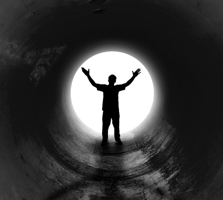 A person is at the end of a dark tunnel with a bright white light shining. The man has his hands in the air for a religious or freedom concept.